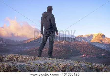 Man on top of mountain standing on the rock watching a nice sunrise in the sunny snowy mountain