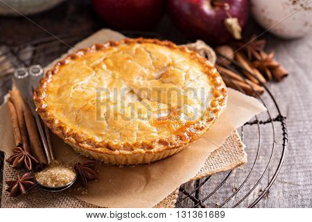 Apple pie with brown sugar and cinnamon on rustic background