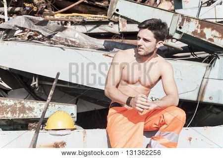 young worker in a junkyard during a break