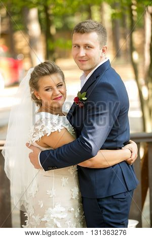 Portrait of happy newly married couple hugging and looking at camera