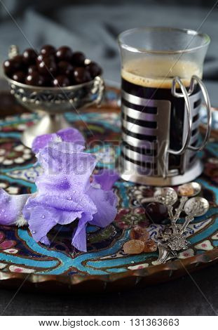 Mug of coffee chocolate drops and iris flower on the oriental tray