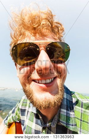 Happy smiling young man guy outdoor. Handsome attractive male in sunglasses.