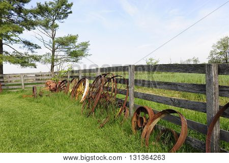 Rusty wagon wheels leaning against a rustic rail fence that's surrounded by grassy fields.