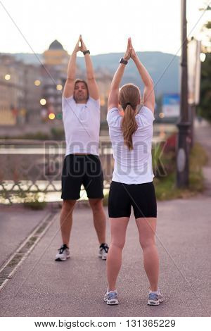 jogging couple warming up and stretching before morning running in the city