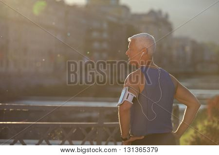 portrait of handsome senior jogging man while relaxing  and take break after morning run