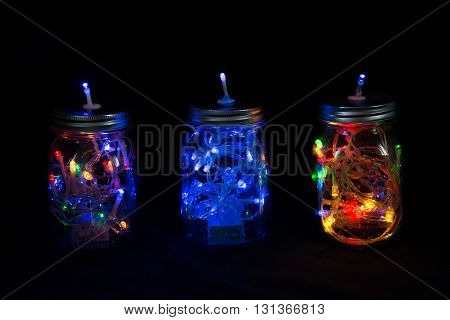 Three mason jars filled with fairylights in three colours