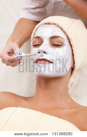 Young woman with clay facial mask. Spa therapy procedure at spa beauty salon