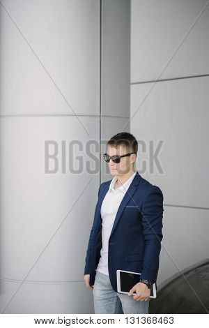 Young businessman keep tablet pc on the street. Portrait of man with dark sunglasses and suit standing near gray wall.