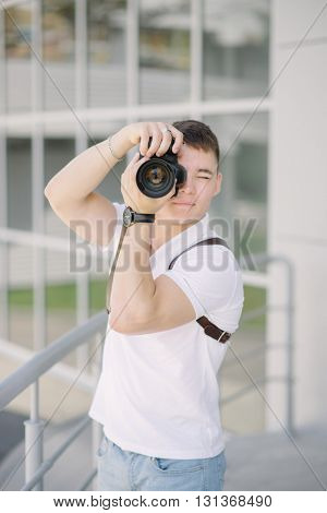 Photographer take a photo. Portrait of young man, tourist with camera in the city. Professional photographer with camera outdoors.