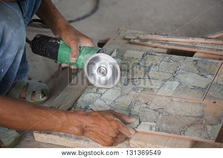 Construction Worker Cutting A Tile Using An Angle Grinder