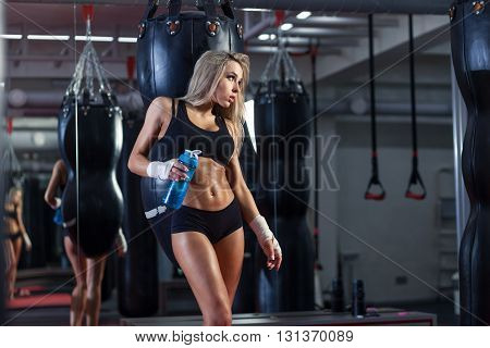 Young blonde boxer woman standing on boxing ring and drinking water from bottle