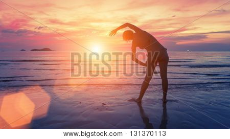 Female silhouette performs physical exercises on the beach after sunset.