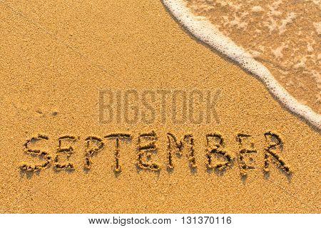 September - written by hand on a golden beach sand.
