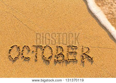 October - written by hand on a golden beach sand.
