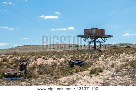 Elevated rusted rainfall water tank on wood platform with stand in a Western Australian farmland landscape with generic vegetation under a blue sky with minimal clouds.