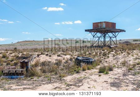 Old rusted water tank on wood platform with stand in a Western Australian desert farmland landscape with generic vegetation under a blue sky with minimal clouds.