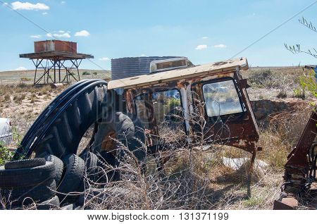 Old tires, rusted car chassis with junk pile and elevated water tank in the background under a blue sky in Western Australian farmland.
