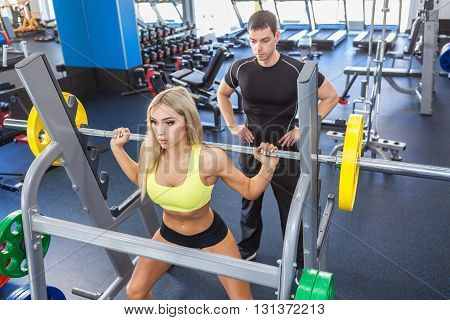 man and blonde woman with barbell flexing muscles in gym. woman and personal trainer in gym