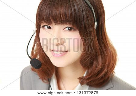 studio shot of young Japanese businesswoman of call center with head sets smiles on white background