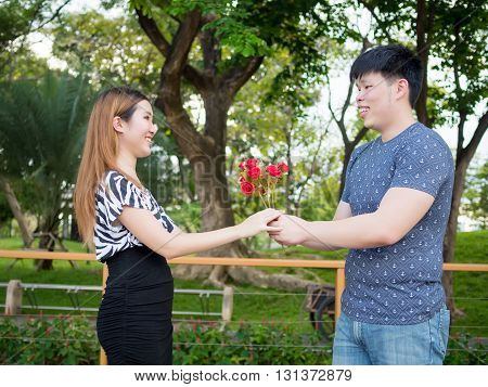 Asian Boyfriend Offering His Girlfriend A Bunch Of Roses In The Park