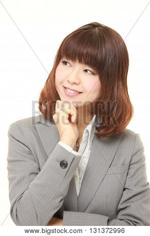 studio shot of young Japanese businesswoman dreaming at her future on white background