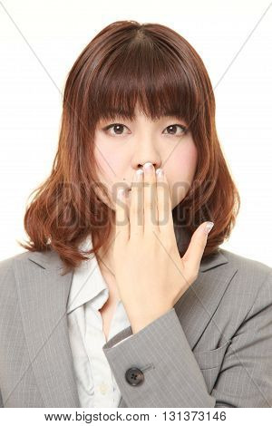 studio shot of Japanese businesswoman making the speak no evil gesture on white background