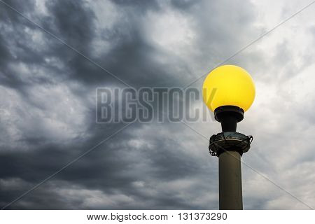 Yellow lamp bright on dark clouds background