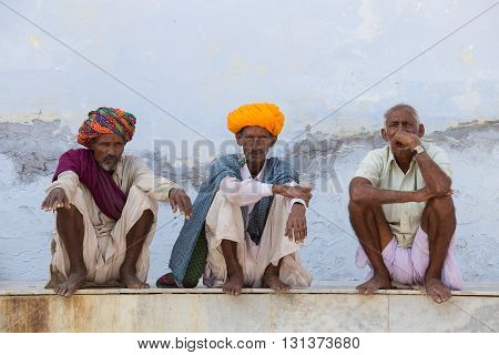 PUSHKAR INDIA - OCTOBER 25 2014: Unidentified Indian men sits on the ghat along the sacred Sarovar lake. Pushkar - famous worship place in India