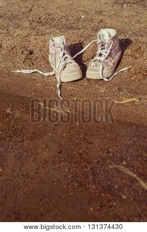 pink gumshoes with long shoelace on the sand