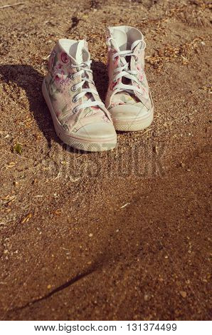 pink gumshoes standing on the sand near the river