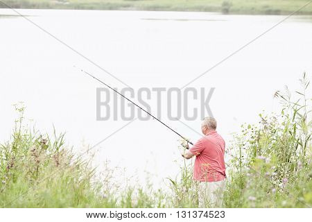Middle aged man wearing polo shirt, angling with rod and spinning reel on summer lake - fishing concept
