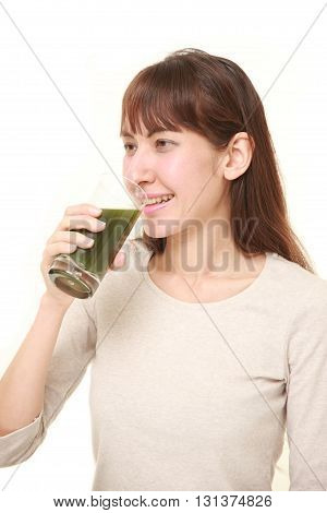 young woman with green vegetable juice on white background