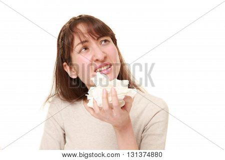 studio shot of young woman with an allergy sneezing into tissue