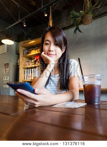 Woman look at mobile phone at coffee shop