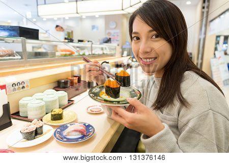 Woman enjoy sushi in restaurant