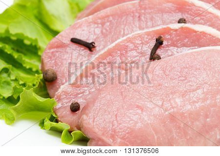Raw beef steak with garlic and black pepper on ceramic plate - on white background