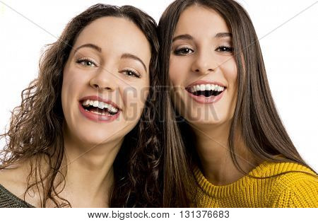 Studio portrait of two beautiful girls smiling