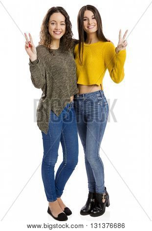 Studio portrait of two beautiful girls with arms open