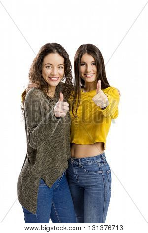 Studio portrait of two beautiful girls with thumbs up