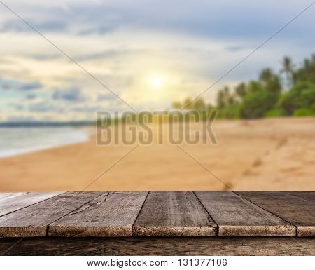 Beautiful sunset on summer sandy beach with palm trees and empty wooden planks, ideal for product placement