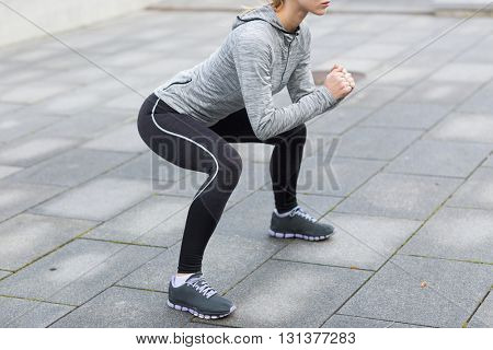 fitness, sport, exercising and healthy lifestyle concept - close up of woman doing squats outdoors