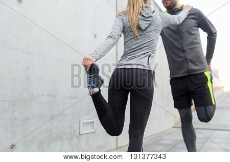 fitness, sport, training and lifestyle concept - close up of couple stretching legs outdoors