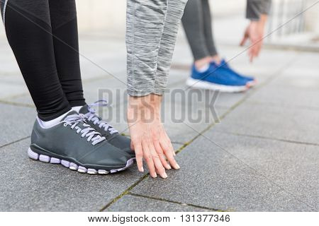 fitness, sport, exercising, training and people concept - close up of couple stretching on city street