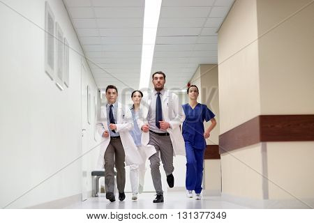 clinic, people, health care and medicine concept - group of medics running along hospital