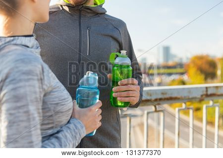 fitness, sport and lifestyle concept - close up of couple with bottles of water outdoors