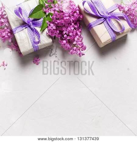 Border from wrapped gift boxes with presents and lilac flowers on grey textured background. Selective focus. Place for text. Square image.