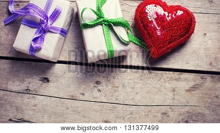 Two festive gift boxes with presents and red shiny heart on vintage wooden background. Selective focus. Place for text. Toned image.