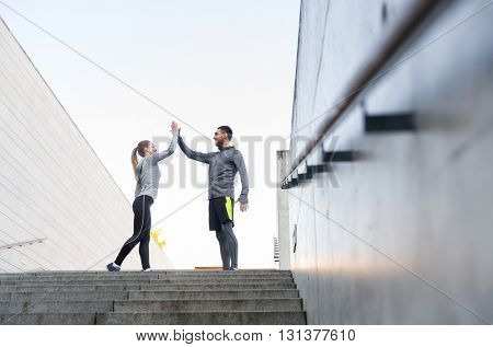 fitness, sport, people and gesture concept - smiling couple making high five on city street