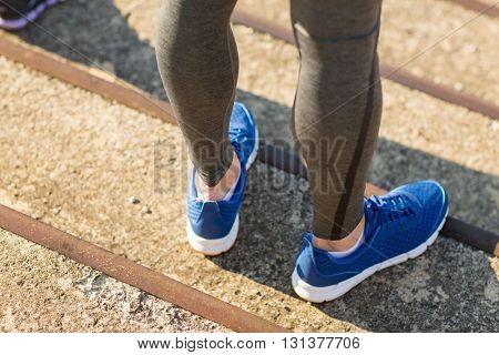 fitness, sport, people and lifestyle concept - close up of sporty man legs in shoes on stairs