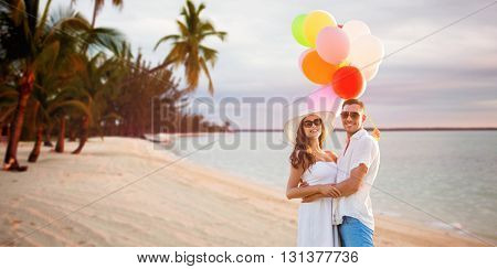 love, travel, summer holidays, relations and people concept - smiling couple wearing sunglasses with balloons hugging over exotic tropical beach with palm trees background